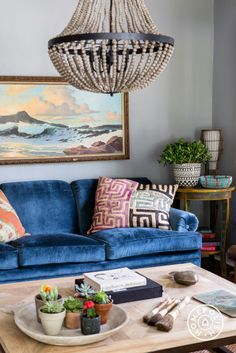 """The living room is more of a parlor room and is quite small but I didn't want to use small furniture because it's the first room you see when entering the home. So, I chose an oversized coffee table and balanced it with a chandelier where a ceiling fan had been."""
