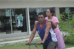 I am not sure whether or not this is a mother and son or Husband and wife but the image shows a startled man cycling in mexico with a woman sitting on the seat behind him.