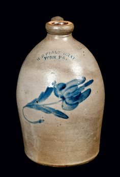 "One-Gallon Stoneware Jug with Cobalt Floral Decoration, Stamped ""H.B. PFALTZGRAFF / YORK PA.,"" circa 1875, semi-ovoid jug with thick spout, decorated with a large brushed-cobalt flower. As-made condition with a stone ping to shoulder. H 11 1/4""."