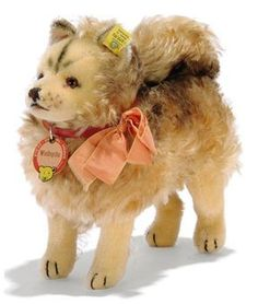 A STEIFF STANDING WOLFSPITZ, (1322,02), long light brown mohair, shorter mohair legs and face, brown markings, brown and black glass eyes, black stitching, inoperative squeaker, red collar, bow, card tag and FF button with yellow cloth tag, circa 1939 --8¾in. (22.5cm.) long