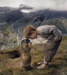 An adorable little boy, a curious marmot, and a dramatic landscape