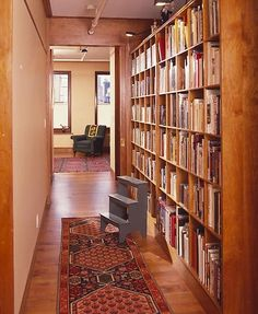 Not an inch of space is wasted in this hallway. Floor-to-ceiling shelves have transformed it into a library.
