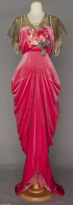 ca 1910 raspberry silk velvet ball gown with netting yoke and sleeves embellished with rhinestones, and one large fabric flower on front bodice. Probably French.