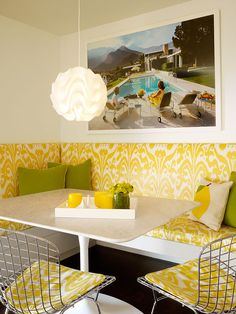 A happy breakfast nook in yellow and white features built in banquette seating with a playful ikat fabric on cushions, a Le Klint pendant light, Bertoia chairs and a white rectangular table with a Saarinen base.    COCOCOZY: DESIGNER ROOM RECREATE: HOW TO MAKE A SUNNY MODERN BREAKFAST NOOK!