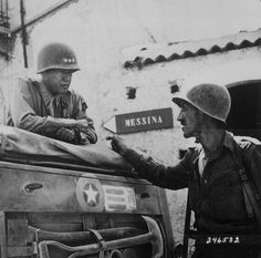 """On July 10, 1943, the Allied invasion of Sicily during World War II began. Taken near Brolo, Sicily, this photograph shows General George S. Patton conferring with Lieutenant Colonel Lyle Bernard. The caption reads: """"Lieutenant Colonel Lyle Bernard, Colorado, 30th Infantry Regiment, a prominent figure in the second daring amphibious landing behind enemy lines on Sicily's north coast, discusses military strategy with Lieutenant General George S. Patton. Near Brolo., 1943 """""""