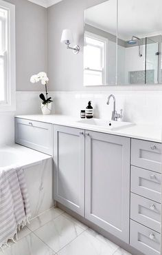 Beautiful gray and white bathroom is fitted with a a gray washstand adorning polished nickel knobs and a white quartz countertop holding an overmount sink with a polished nickel gooseneck faucet in front of white subway backsplash tiles tiled with white pencil tiles fixed beneath a vanity mirror flanked by nickel sconces mounted on a gray wall.