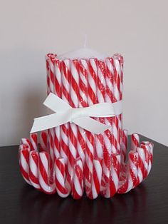 Candy canes around a candle and tied with ribbon. Easy holiday decoration or center piece!