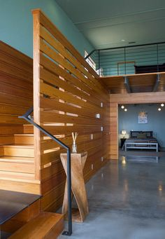 horizontal slatted stair wall -- speaks to log wall opposite but also keeps it open...?