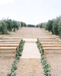 If you're going for a fresh and minimal look, keep your ceremony space simple with just a few benches and a garland of greenery running all the way down both sides of the aisle.