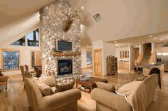 Vaulted ceiling hangs over centralized stone fireplace surround, with natural wood seen throughout on doors, cabinetry, and framing. Natural hardwood flooring compliments the look, with an array of beige corduroy and brown leather seating. Small Living Room Design, Family Room Design, Living Room Colors, Living Room Designs, Family Rooms, Stone Fireplace Surround, Fireplace Design, Fireplace Ideas, Fireplace Screens