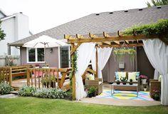 pergola moderne en bois de design autoporté décorée de rideaux blancs, plantes grimpantes et accessoires assortis