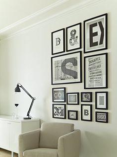 Pared decorada con composición de cuadros con marcos negros