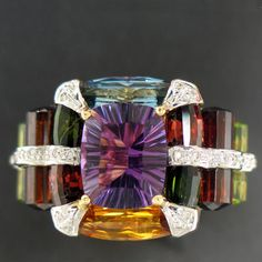 From the Bellari collection, a ladies 18k Yellow Gold ladies ring. Amethyst center with multi colored gemstones & diamonds.