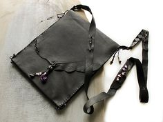 iPad sleeve in black leather with shoulder strap, in style of tribal talismanic pouch