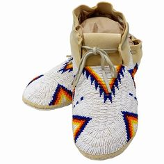 $330.00 Beaded White Moccasins: Men's Size 11 1/2. These men's moccasins just came in by local bead artist Jessie Pretty Hip. Jessie is a member of the Oglala Lakota Sioux tribe of South Dakota. She resides in the small town of Porcupine on the Pine Ridge Indian reservation.