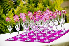 Champagne glasses with purple orchids. From Hawaiian event design company Yvonne Design