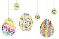 Blanko-Eier und große Ostereier mit Wattestäbchen bunt bedruckt.