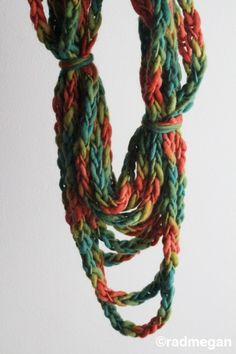 Can't find instructions on the website, but this looks like a really long crocheted chain, looped to desired length, then tie in various places to hold its shape.  I might stitch down the randomly tied areas first, just to prevent slippage.  I know some girls who could rock this!