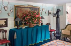 Bilhuber combines formal elements, like a Prussian-blue skirted table, with simply potted flowers to achieve a handsome entrance hall at his Long Island, New York, country house, Hay Fever.