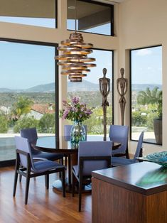 Large windows bring tons of natural light into this contemporary dining room. Blue-gray chairs are paired with a simple, round table, but the star of the space is the cylindrical chandelier. Luxury Dining Room, Dining Room Design, Dining Rooms, Dining Tables, Modern Room, Modern Decor, Contemporary Decor, Room Interior Design, Dining Furniture