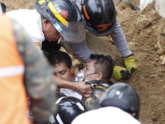 A firefighter is rescued after he was trapped while working at the site of a landslide in Santa Catarina Pinula, Guatemala. A hill collapsed late Thursday after heavy rains, burying several houses with dirt, mud and rocks. The death toll rose to 30 amid fears that hundreds more could still be buried in the rubble.   Luis Soto, AP