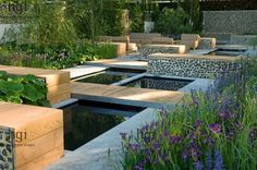 Harpur Garden Images :: 07jh103 The Savills Garden. Silver Gilt. Clean lines simplicity of form. Contemporary. Modern. Conceptual low dividing flint walls water feature pond pool decking deck decked path boardwalk hard landscaping Design: Marcus Barnett & Philip Nixon RHS Chelsea Flower Show 2007 UK Jerry Harpur