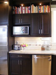 subway tile, and dark cabinets. Nice way to use the space above the cabinets