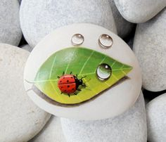 Painted stone ladybug on a leaf by KanetisStones on Etsy