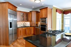 Kitchen design: The stainless steel oven, refrigerator, dishwasher and separate convection oven/microwave are all built into the cherry cabinets to maximize floor space. A five-burner range with retractable hood is the centerpiece of the granite-topped island.