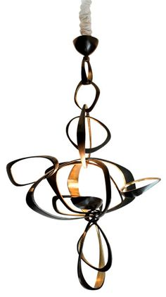 I love the black/bronze combo. Not only is it sculptural, I can see sparkles of warm light bouncing off the walls of whatever room this hangs in.