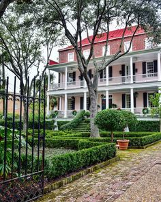 Old Charleston Homes and mansions and southern architecture -  cobblestone driveway and walk, pristine landscaping, 2 front porches, painted pink with black shutters, iron gate - historic home. Single Christmas wreath on each window and front door - holiday decor  #charleston #porch #porchideas #holidaydecorations #architecture #pink #exteriordesign #christmasdecor #exterior #architect #architecturelovers #architecturehouse #architecturephotography #holidaydecor