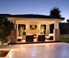 Luxurious outdoor entertainment space. Comfy lounge chairs, TV above a fireplace and great stonework.