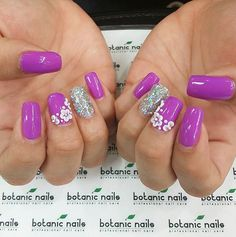 Beautiful Purple nail art design with embellishments. Make your nails look out of this world by adding glamorous glitter polish on one side while covering the other nails with beautiful white flower embellishments on top.