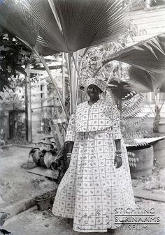 Kotomisi in een tuin. Het motief van haar koto is trowlinga (trouwringen).  Datum: rond 1910 Locatie: Paramaribo, Suriname