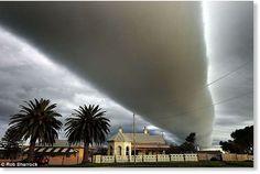 Eine unglaubliche Roll Cloud beherrscht den Himmel über dem Haus des Fotografen in Australien. Roll clouds treten vor Sturmfronten auf.