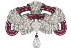 omposed of a pavé-set buff-top ruby frame interwoven with a pierced stylised single, old and baguette-cut diamond-set ribbon, to the central...