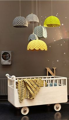 Love this idea of hanging different sized shades o some kind grouped together like this. Maybe not over a crib but in a kids room, play room or really anywhere depending on the shades u use.