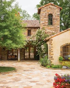 A variety of elements compose the exterior of the guesthouse including stone, a roof made from reclaimed Italian tile, and rough-hewn wood. The neutral structure stands in contrast to the lush, verdant landscape. | At Home in Arkansas | March 2016 | A Bountiful Beauty | Outdoor Living | Italian Style Home