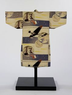 In the 1930s kimono for young boys, such as this example, were often patterned with highly graphic propaganda images. Unusually, this kimono commemorates an actual event, the first aeroplane flight from Japan to Europe. The plane, called the 'kamikaze-go' flew from Tokyo to London, landing at Croydon airport on April 9th 1937 making its pilot, Masaaki Iinuma, a hero.