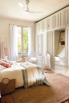 El dormitorio. Cojines y colcha a rayas de El Meu Coixí. Manta de Matèria y alfombra de Francisco Cumellas. Silla de Coton et Bois.