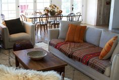 Chay's Lake Hollywood Spanish House Tour | i love the neutrals and textiles.  sofa textile, the orange pillows, leather pouf are so inspired