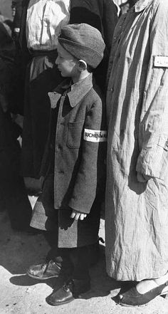 A six-year-old orphan, with a Buchenwald armband, stands in the roll call line at Buchenwald camp, Germany