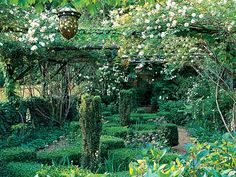 Boxwood beds set on a diamond pattern extend between gravel paths beneath a pergola of rough timbers. Climbing roses add to the romantic appeal of the scene. (Photo: Roger Foley)
