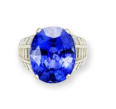 A sapphire and diamond dress ring, by Asprey Claw-set with a large oval mixed-cut sapphire, weighing 22.14 carats, the bevelled hoop and gallery channel-set with tapered rows of baguette-cut diamonds and highlighted with four kite-shaped diamonds, diamonds approximately 5.50 carats, signed Asprey, maker's mark and French assay marks.