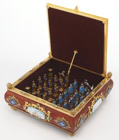 A Hungarian silver-gilt and enamel chess set, 20th century the wood box with enameled plaques of naval scenes in scrolling foliage surrounds at the sides, the top set with turquoise glass beads and pearls, with openwork finials at the angles, the top lifting to store the pieces, one side in silver with enameled light blue coats, the other side gilt and enameled in dark blue marked 925 on front of upper mount