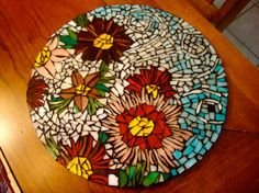 """Stepping Stone - 12"""" round mosaic with flowers and whimsical designs. It is an original piece, as with all of my work."""