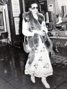 Style icon, Bianca Jagger in a boho embroidered maxi dress and fur stole
