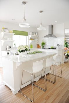 Maria Killam's White Kitchen - After (white subway tile, white cabinets, range vent hood - no microwave, pendant island lighting, wood flooring)