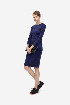 ELASTIC DRESS Shorthaired model wearing a tight fitted blue dress with an original black print, a minimalistic leather clutch bag and black sneakers. Design: Lucie Kutálková / LEEDA