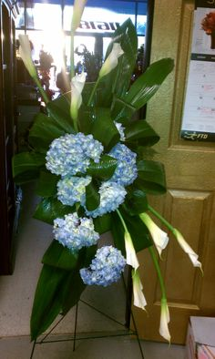 Funeral easel of Calla lilies and blue hydrangea accented with tropical greens starting at $175.00
